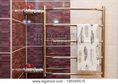 A white towel is dried on the heated towel rail in the bathroom. Towel warmer in bathroom