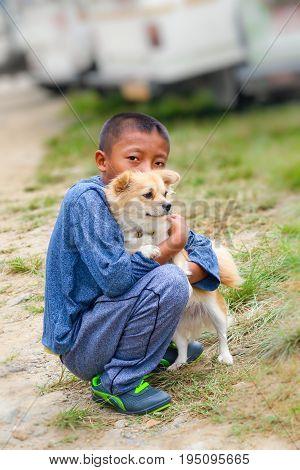 Lobesa Village, Punakha, Bhutan - September 11, 2016: Bhutanese Boy Hugging A German Spitz Puppy In