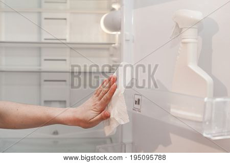 House cleaning - spray bottle with detergents for washing the fridge. The housekeeper wipes the shelves of a clean refrigerator with a dry napkin. Young woman cleaning refrigerator