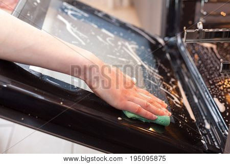 Housework and housekeeping concept. Scrubbing the stove and oven. Close up of female hand with green sponge cleaning the glass door of kitchen oven.