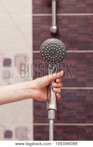 Housewife holds in her hand cleen and сlosed off rain shower head in the bathroom.