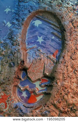 Reflection of the American flag on the footprint of the boot in the ground
