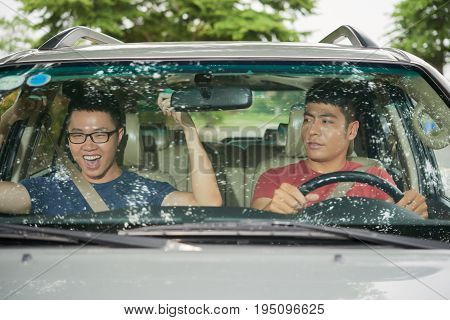 Unforgettable road trip: cheerful Vietnamese man sitting on passenger seat and dancing to his favorite song while his best friend driving car and looking at him with surprise, view through windshield