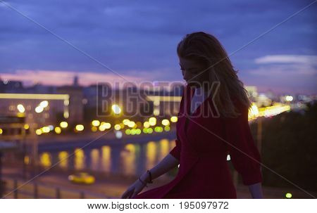 Gold time shooting. Young beautiful woman in a long red dress is sitting on a parapet. Sunset in Moscow. High angle view of the city and the river.