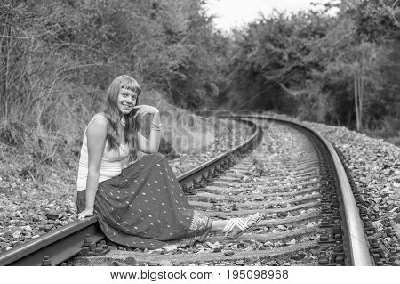 Young lady in red dress sitting on railway tracks