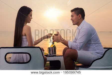 Asian couple in romantic dinner with sea beach and sunset in Thialand island. love valentine summer and honymoon concept.