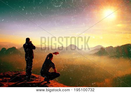 Film grain effect. Hiker and photo enthusiast stay on cliff and thinking. Dreamy fogy landscape blue misty sunrise in a beautiful valley below