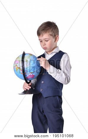Standing schoolboy hold a globe of world and searching something on it, isolated on white backgroudn