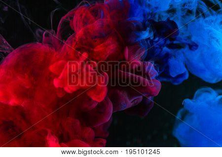 Abstract background Splashing smoke color texture in the air. Smoke fragments isolated on dark background lowkey lighting.