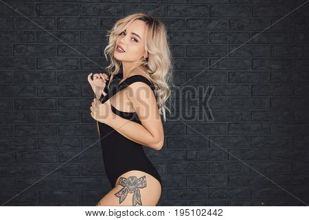Attractive Blonde With Tattoos Posing On A Black Brick Wall Background
