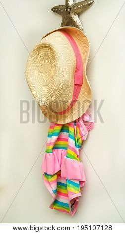 Swimsuit and beach hat hanging on a hook