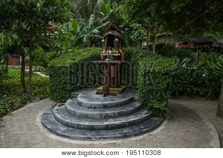Traditional Thai spirit house against Green tropical tree