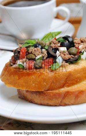 Fried toast with chopped tuna with egg cubes of tomatoes and olive slices capers