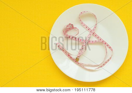 Tapeline on white empty plate on yellow yoga mat. Weight loss and diet concept