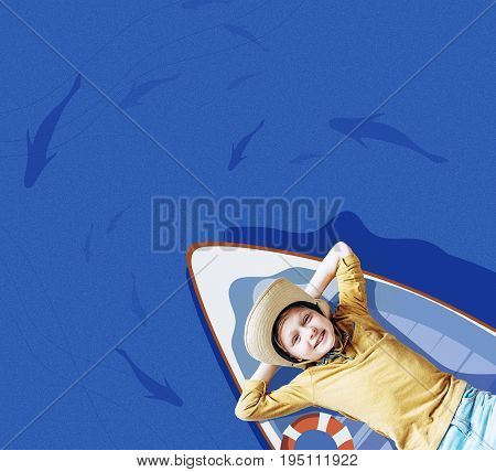 Top view of cute little boy in hat lying on floating boat and smiling
