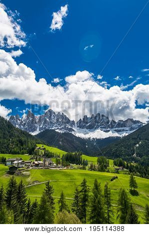 Looking towards the stunning Alpine mountain of Ortisei with blue sky and white clouds, an awesome view of the beautiful Dolomites can be seen in the distance, Northern Italy, Europe