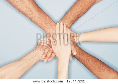 Closeup of multiethnic men and women piling hands on top of each other against blue background