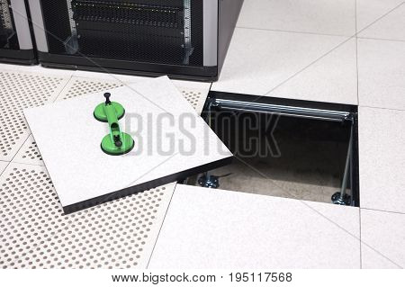 High angle view of lifted floor tile with vacuum suction cups in datacenter