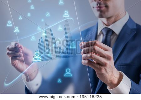 Business technology internet and communication computer network concept. Pleasant young businessman is holding transparent screen of future and working with it