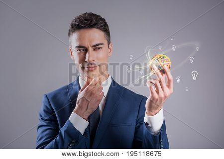 What ideas should I choose. Portrait of elegant pleasant businessman is expressing thoughtfulness while looking at little colorful ball in hand and touching his chin. Creativity concept