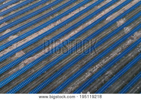 Series of solar cells located on the field in the suburbs. Aerial view. Alternative sources of energy.