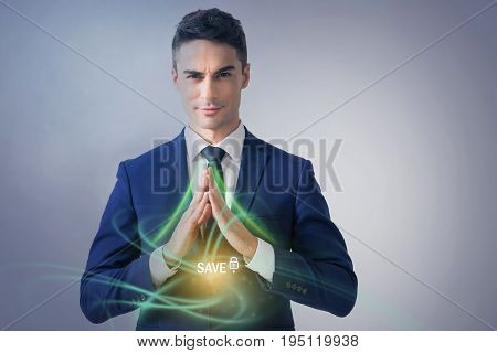 Data protection concept. Portrait of young successful man wearing suit is expressing confidence while looking at camera with positive emotions