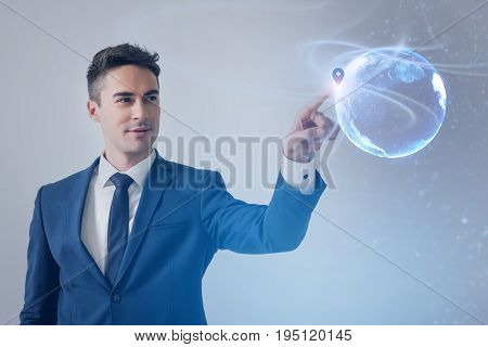 Geolocation info. Young positive businessman wearing suit is pointing on location on 3D model of globe. Pleasant man is standing with slight smile