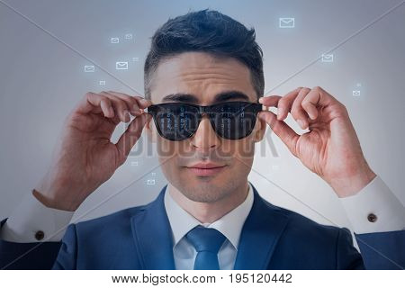 Communications concept. Portrait of pleasant elegant young businessman is touching his sunglasses with reflection of numbers while standing with message icons which are flying around his head