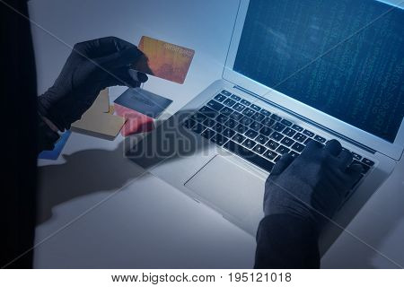 Electronic banking security concept. Close up top view of hands of hacker wearing gloves. Burglar is stealing money from credit card using laptop while sitting at desk