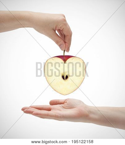 Picture of apples in the shape of hearts and two hands