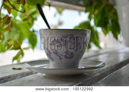 Tea cup whit spoon on wooden bench at the beach