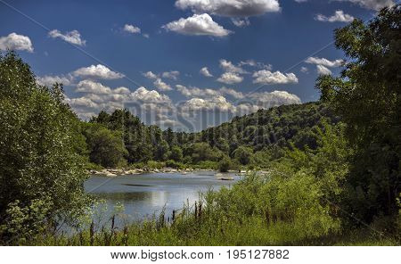 White fluffy clouds swim over the river in the blue sky very rarely. Overgrown with greenery of the river bank. White stones lie in the water of the river.