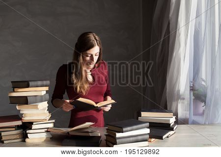 girl reads a lot of books at home at the table