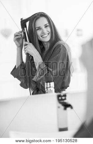 Smiling modern woman curling hair with straightener