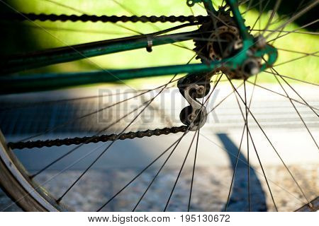 Bicycle chain on old dark green bike with light green lawn