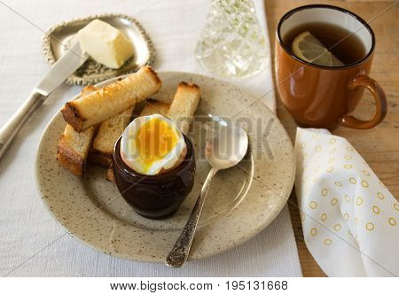Breakfast, boiled egg, croutons, butter and tea
