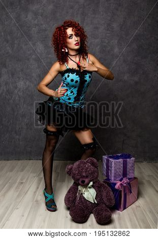 Curly redhead sexy girl looks like a doll for adult men. popsy posing with teddy bear and gift box.