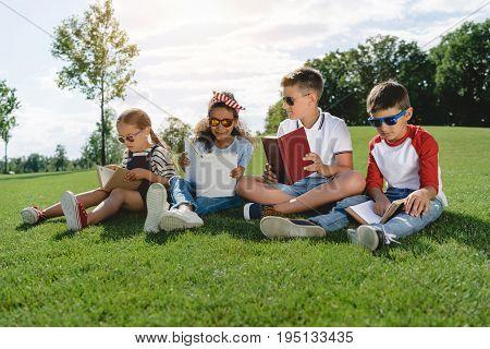 Cute Multiethnic Children In Sunglasses Reading Books On Green Meadow