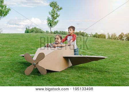 Cute little children playing with diy plane on green meadow in park