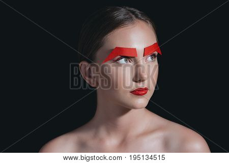 Portrait Of Beautiful Woman With Red Lips And Paper Brows Posing For Fashion Shoot Isolated On Black