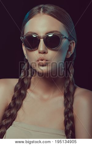Portrait Of Grimace Woman With Braids In Sunglasses Isolated On Black