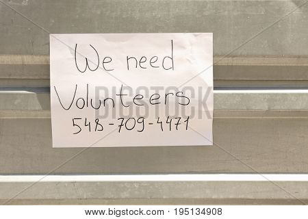 Announcement with text WE NEED VOLUNTEERS on metal fence