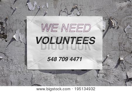 Announcement with text WE NEED VOLUNTEERS on grunge wall
