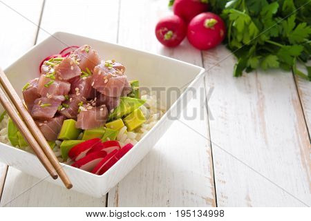 Hawaiian tuna poke bowl with avocado, radishes and sesame seeds on white wooden background