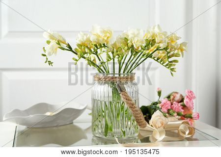 Beautiful bouquet of fresh freesia in vase on table