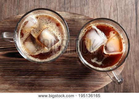 Glass cups of cold brew coffee on wooden table