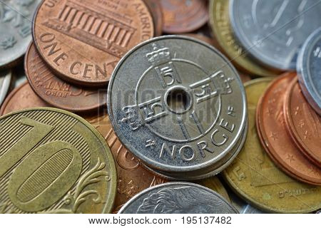 Macro detail of five Norwegian Crowns (NOK) on the top of heap made of many diverse currencies as a symbol of international trading with Norway