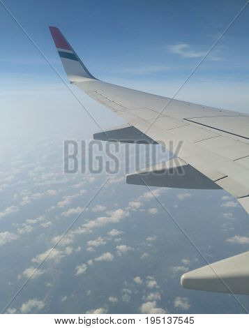 Aeroplane wing in blue sky and white clouds