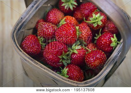 Garden Strawberries in wooden basket isolated on wooden background