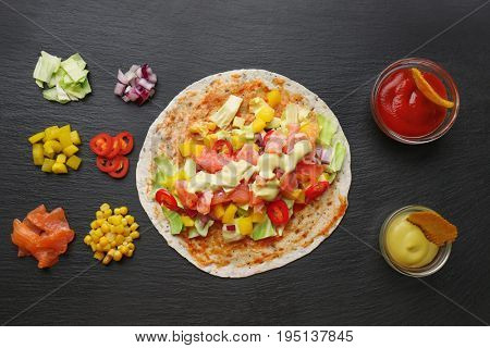 Ingredients for fish tacos on dark background